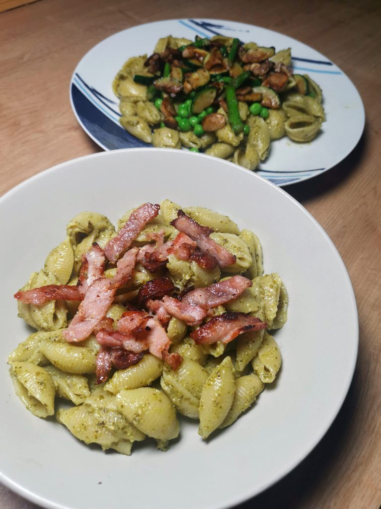 Both versions of pesto pasta - bacon in foreground and spring vegetables in background