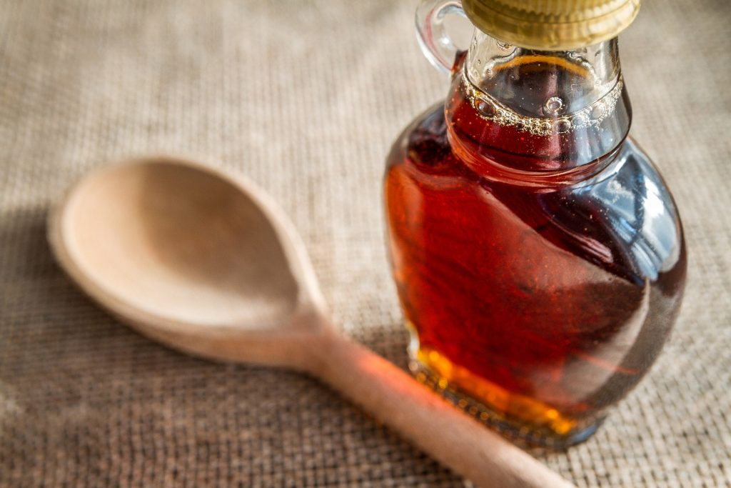 Bottle of maple syrup with wooden spoon