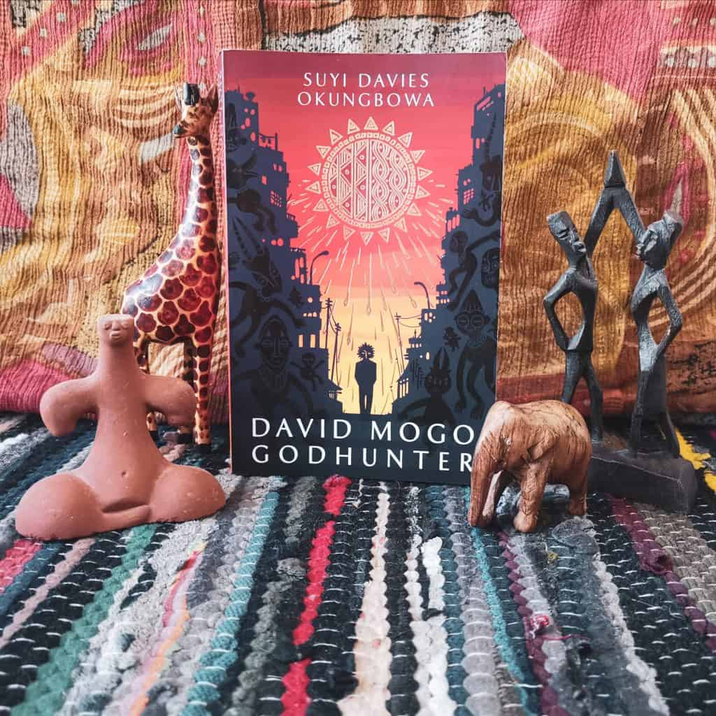 Title for Afrofuturism literature David Mogo Godhunter - the book alongside African people and animal figures against a warm coloured pattern background