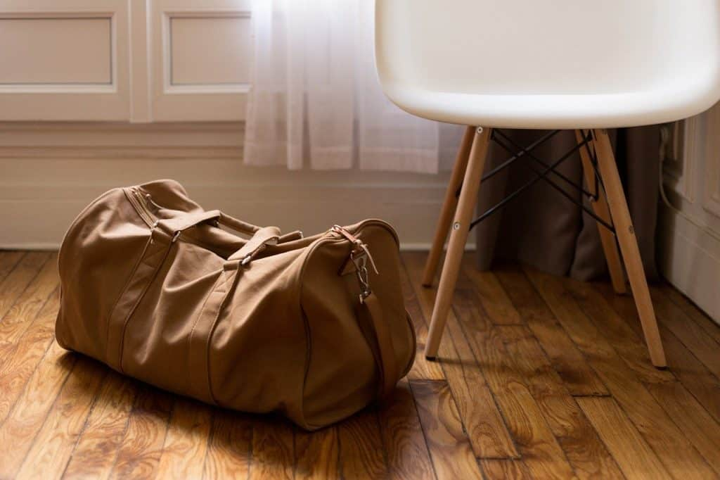 Brown duffel bag on wooden floor next to white chair