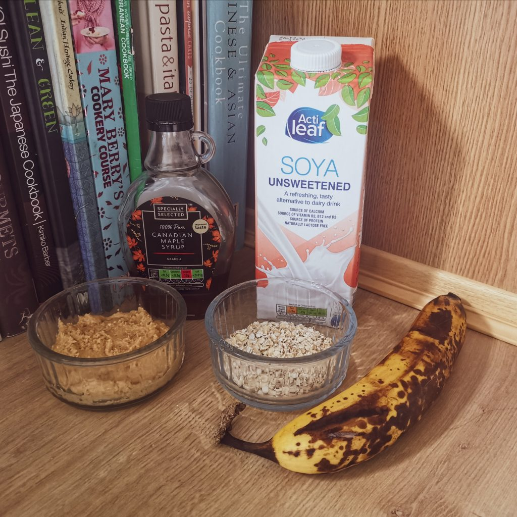 Ingredients for the smoothie - maple syrup, soya milk, peanut butter, oats, and a ripe banana
