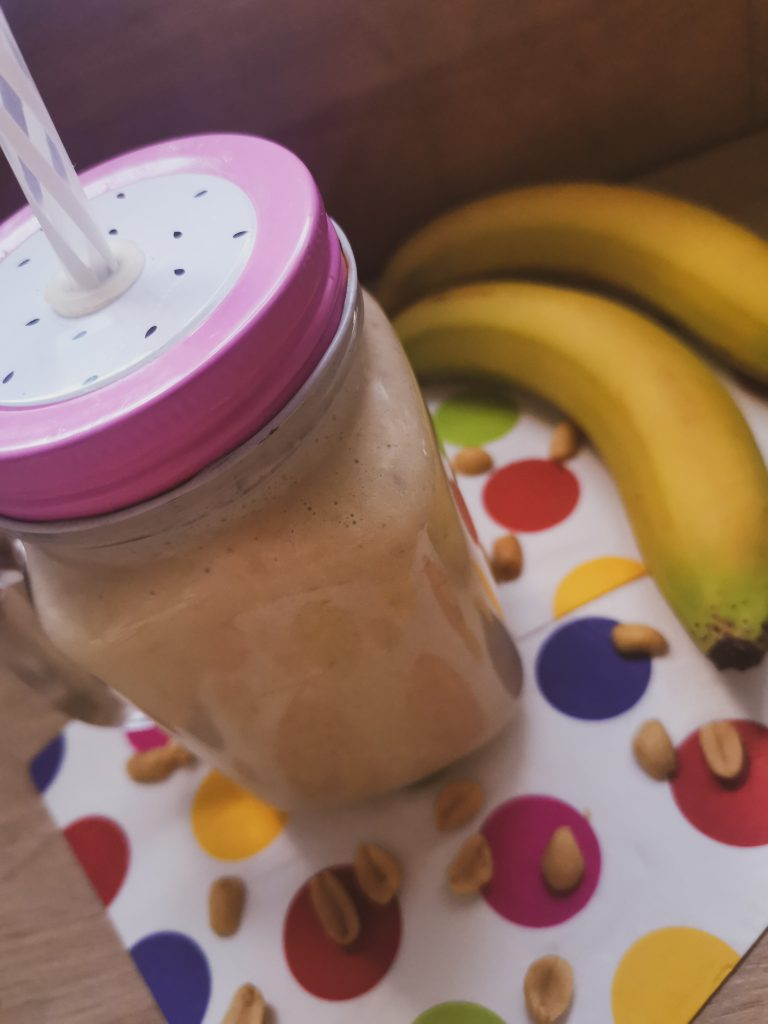 Finished smoothie in a jar next to bananas and loose peanuts