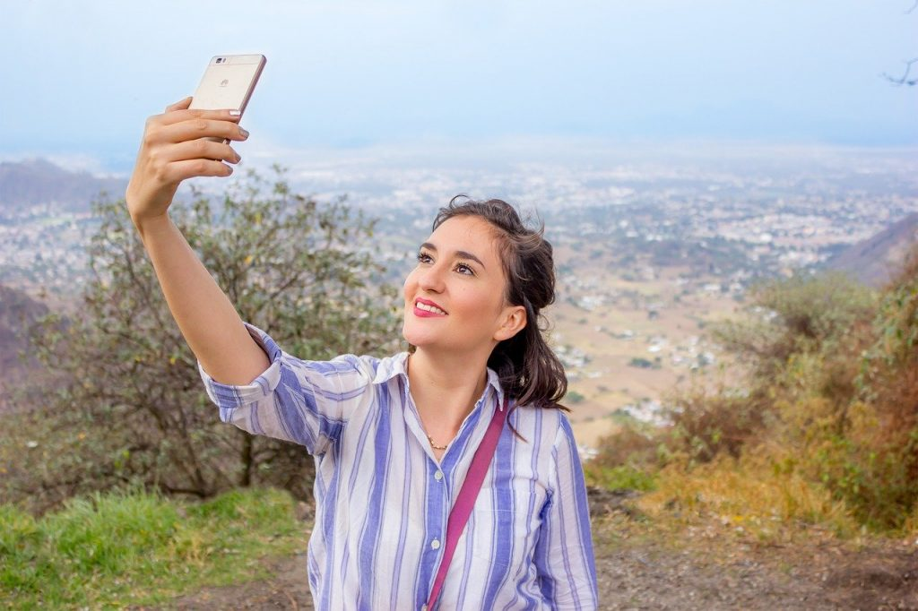 Woman taking selfie in rural area atop cliff