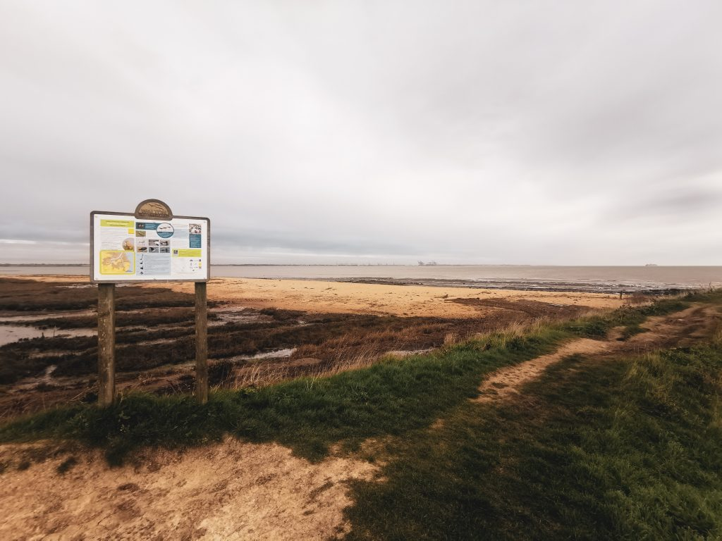 View of the beach on the Walton Backwaters route with information sign
