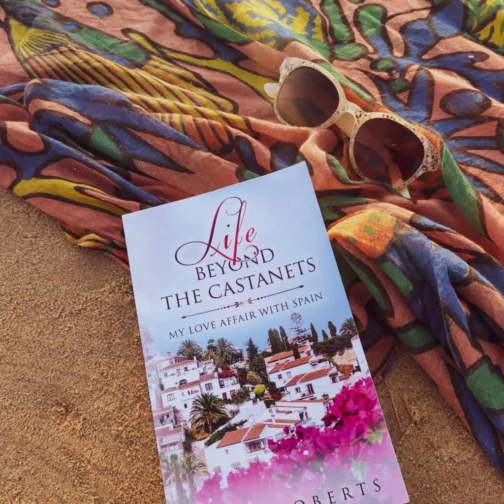 Title image for Life Beyond The Castanets, second of Jean Robert's travel memoir books - book on sand with colourful sarong and sunglasses