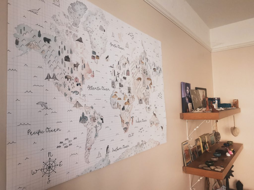 Another angled photo of one of world map prints with decorated shelves in background