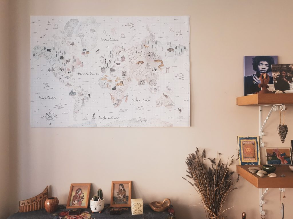 One of Photowall's world map prints on wall surrounded by other shelf decor