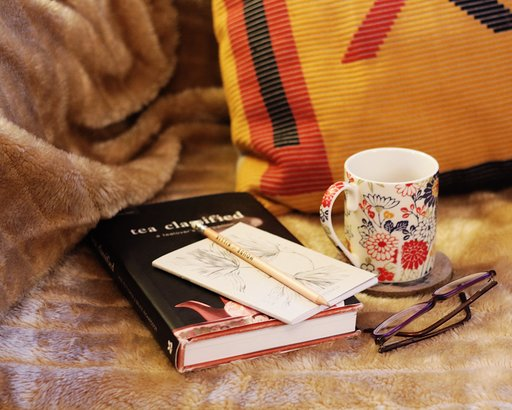Book and cup of tea resting on blanket with a sketchpad, pencil, and folded up glasses