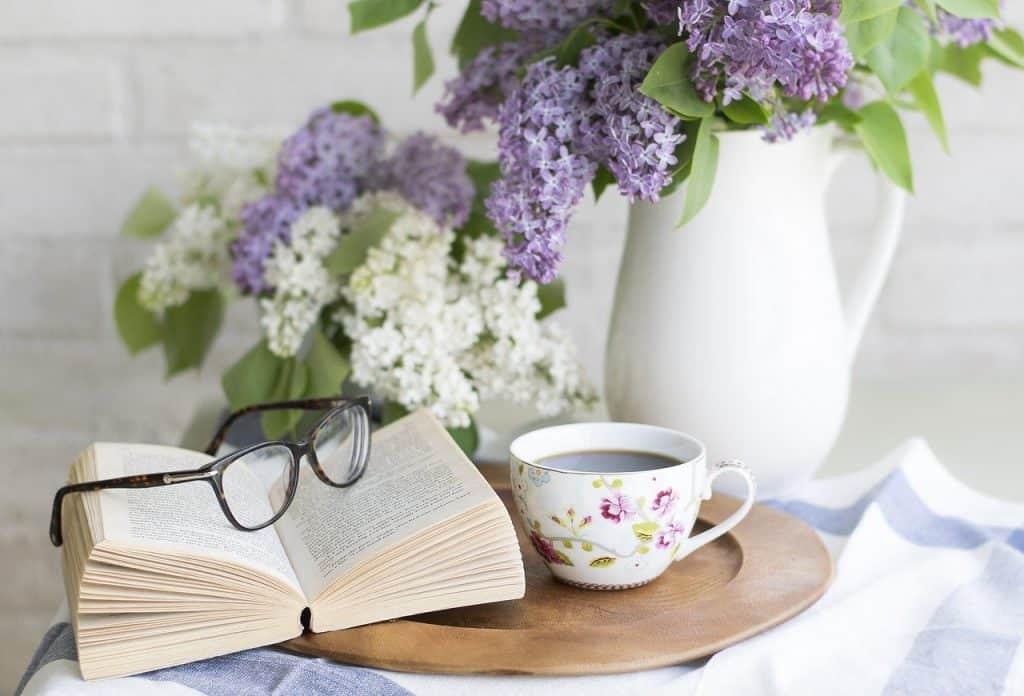 Open book with glasses on top on a tray with a floral cup of coffee and white and purple flowers in the background