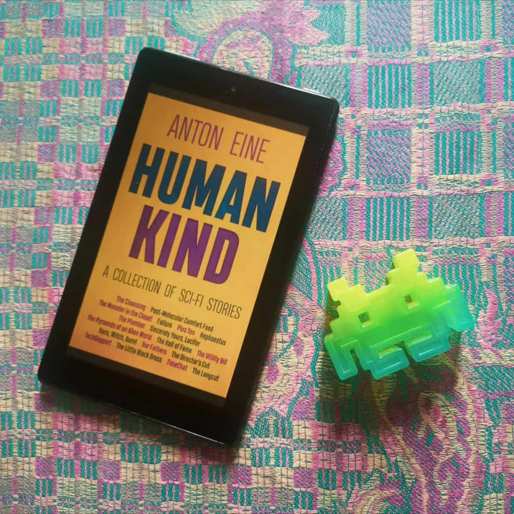 Flatlay photo of Human Kind collection of sci-fi short stories on Kindle next to a Space Invaders figurine with a paisley turquoise and magenta material background