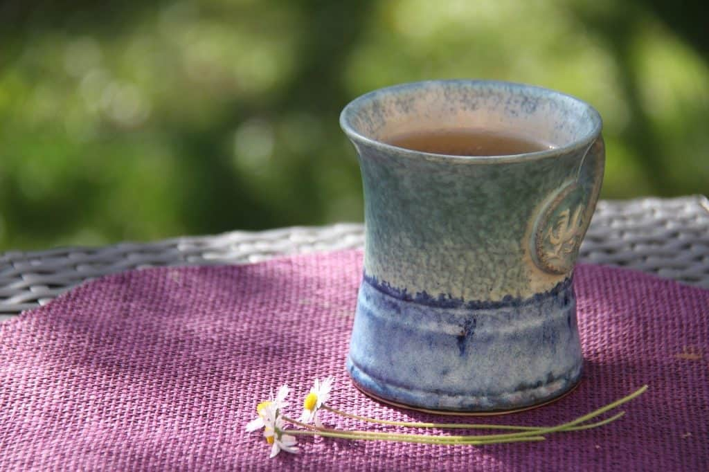 Close up of a blue mug of tea on an outside table with daisies placed next to it