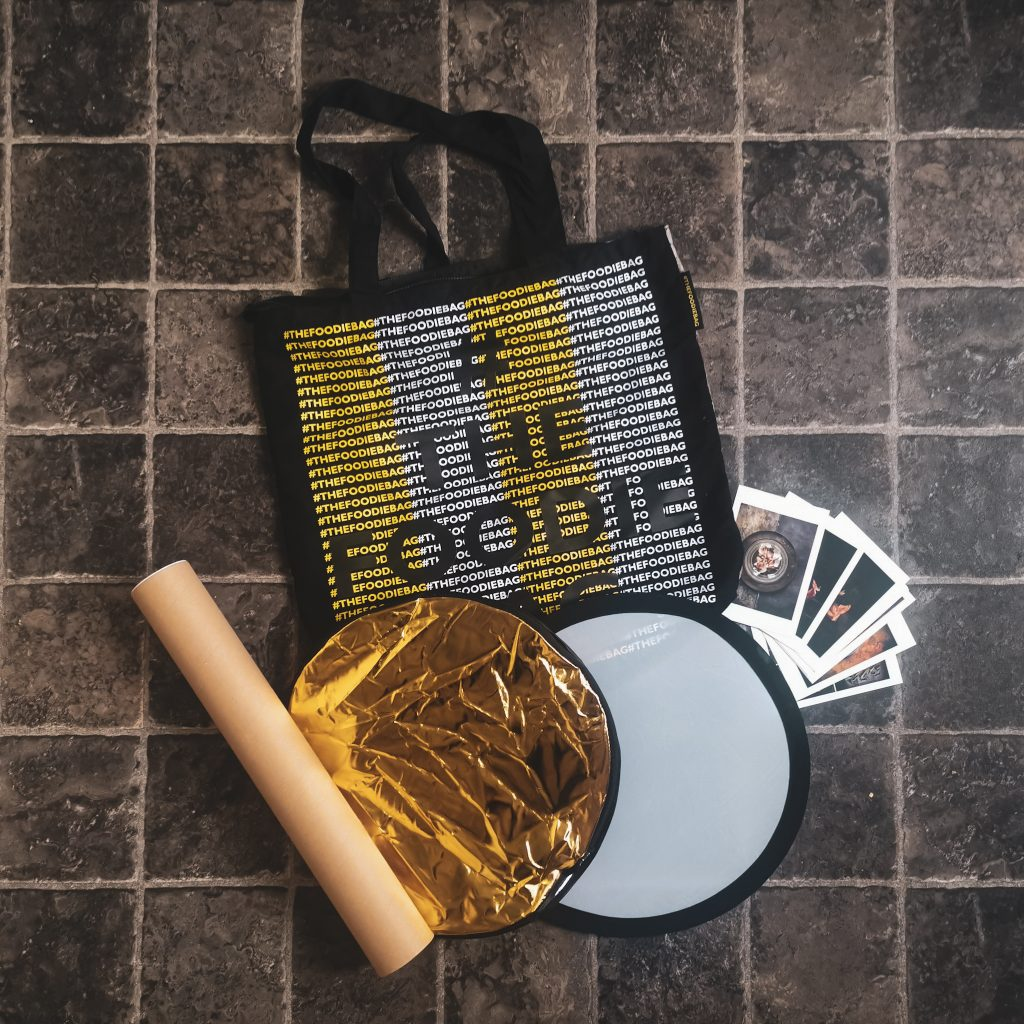 Title image for The Instagram Bag Food Photography Tricks - contents of bag (diffuser, reflector, cardboard roll, postcards) and bag in aerial shot