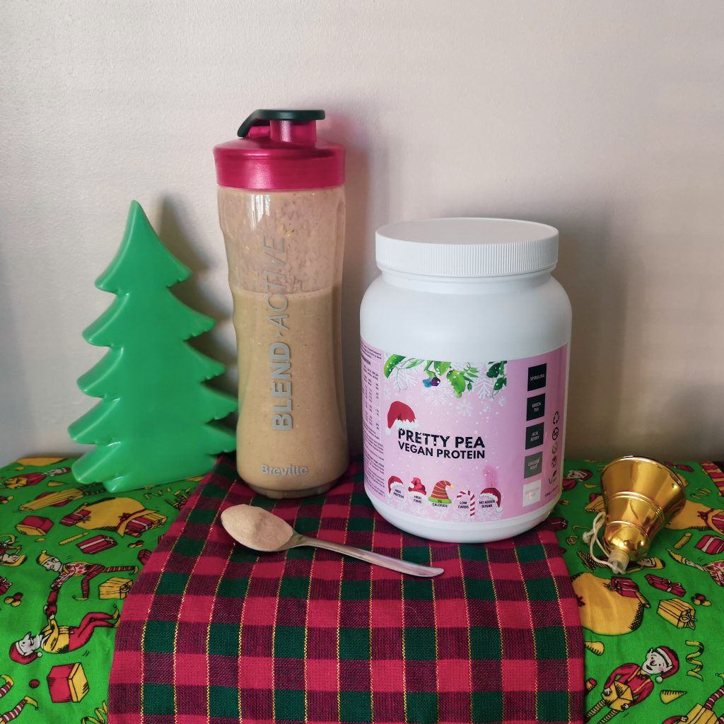 Vegan gift ideas - image of Pretty Pea Protein tub and spoon of protein powder next to smoothie and Christmas decorations