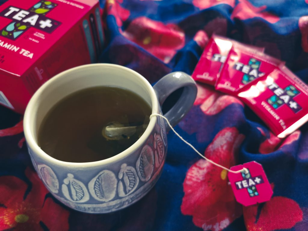 Cup of tea from Tea+ with pink teabags and box in background - vegan gift ideas