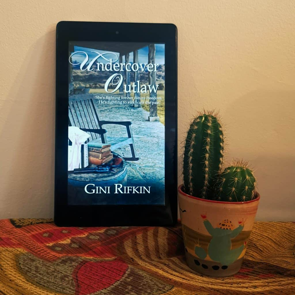 Cover image for Undercover Outlaw, one of Western romance novels by Gini Rifkins - cover image sits on orange, yellow, and brown patterned clothed table next to a tall cactus with two heads (one large, one small) planted in a cactus desert-themed small plant pot