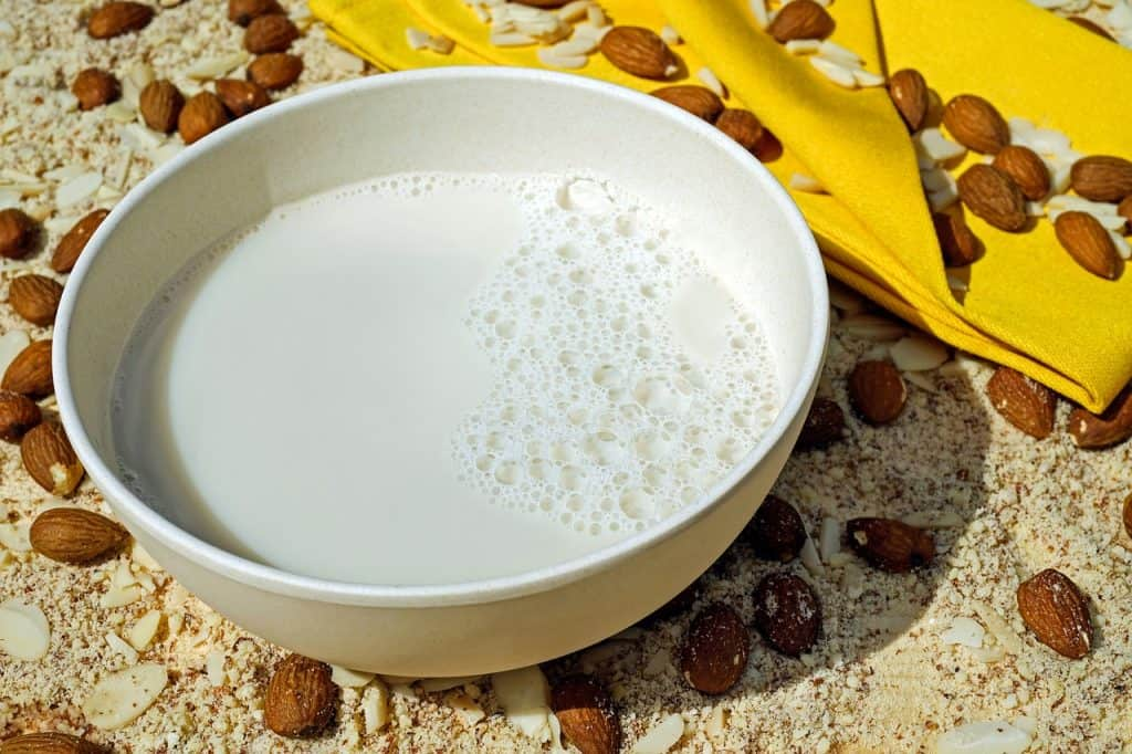White bowl of almond milk next to yellow folded cloth, surrounded by whole and sliced almonds
