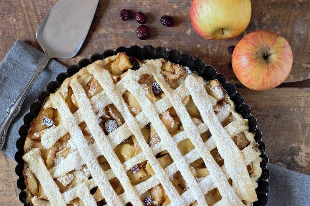 Title image for Vegan Baking Alternatives - aerial view of latticed apple pie with serving spoon on left and two apples on right