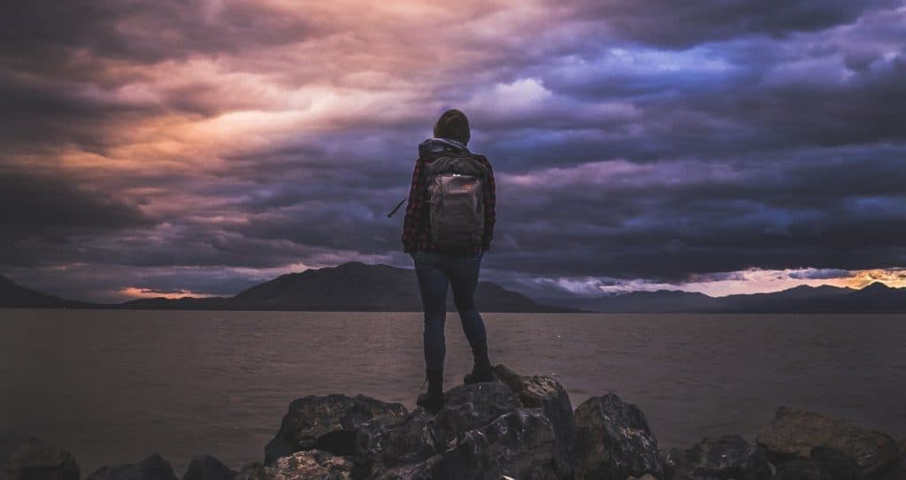 Title image of Learn To Travel Solo Successfully: Hiker standing on rocks facing away towards a lake and mountains in the background beneath a dramatic, cloudy sky