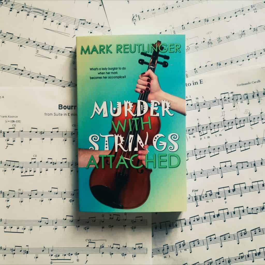 Title image for cosy mystery novel Murder With Strings Attached by Mark Reutlinger - top-down photo of book placed on various pages of sheet music