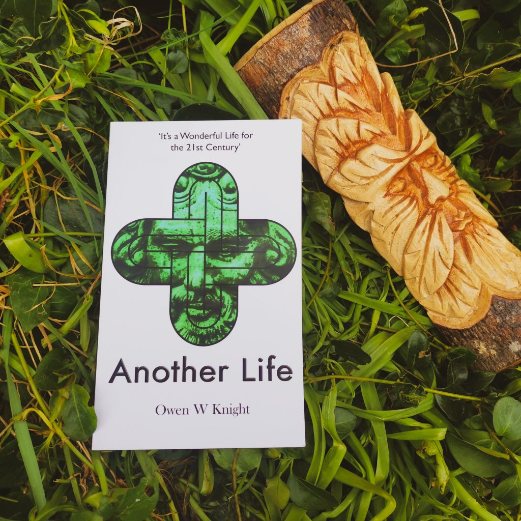 Title image for Another Life - top lay shot of book placed on grass with carved Green Man figure to the top right