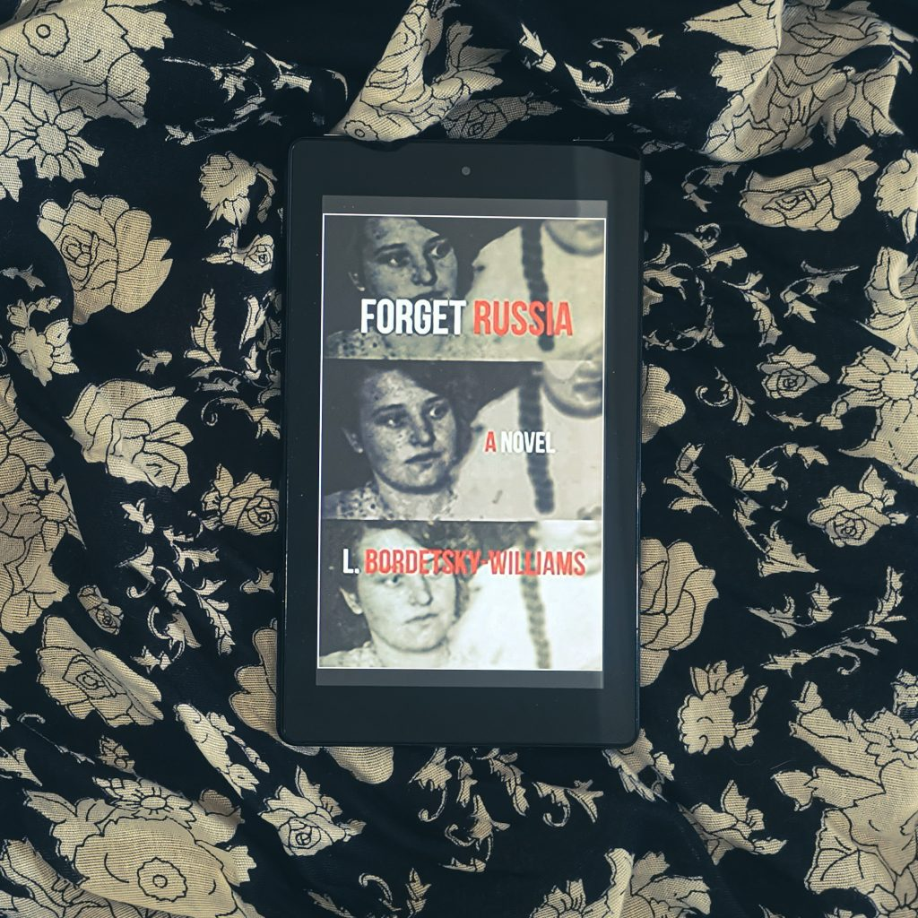 Title image of historical fiction novel Forget Russia - overlay shot of Kindle with book cover placed on black and white floral material
